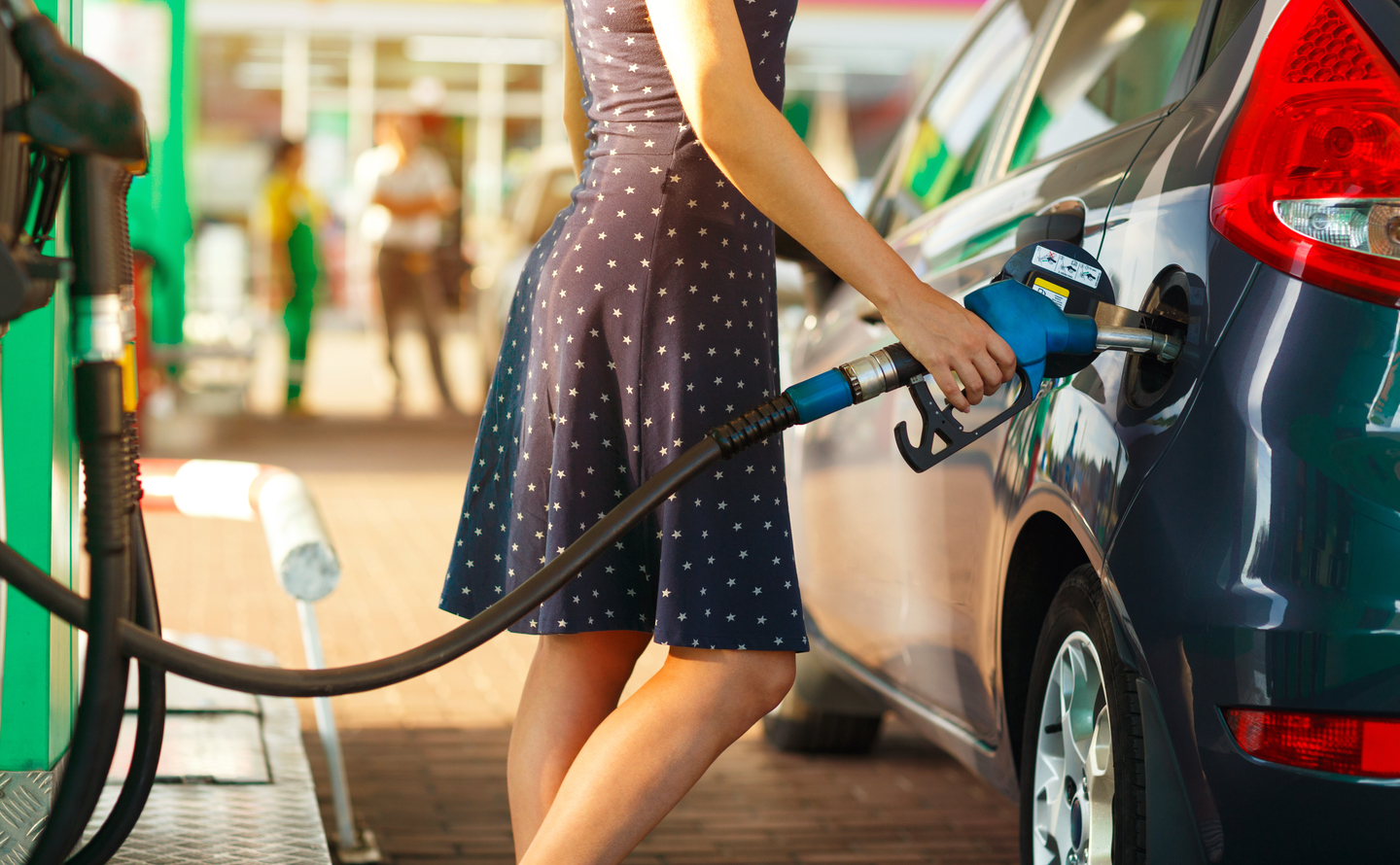 Car Maintenance Tips: Woman fills gas into her car at a gas station